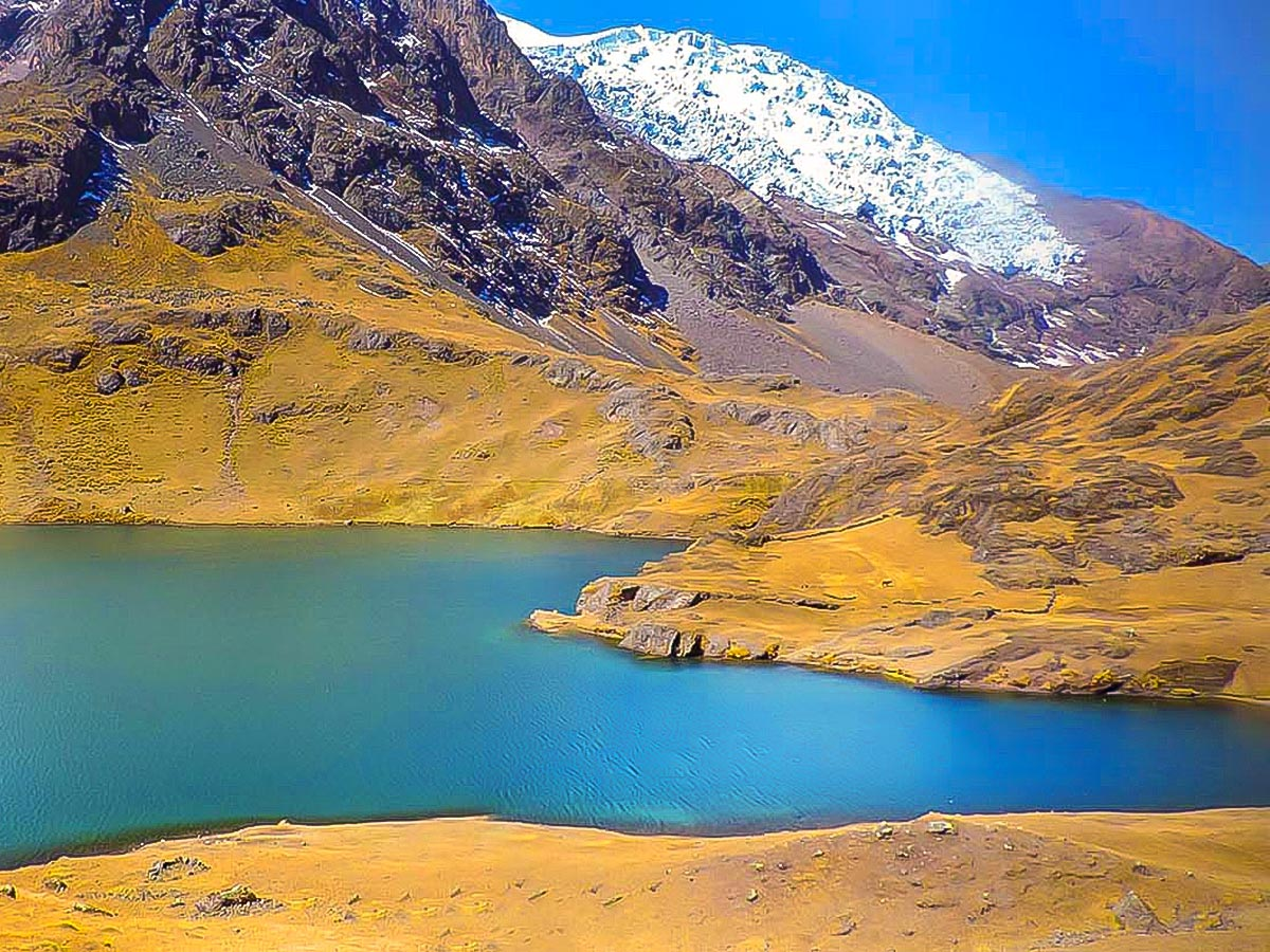 A bright blue lake surrounded by yellow hills and a snow-covered mountain in the distance