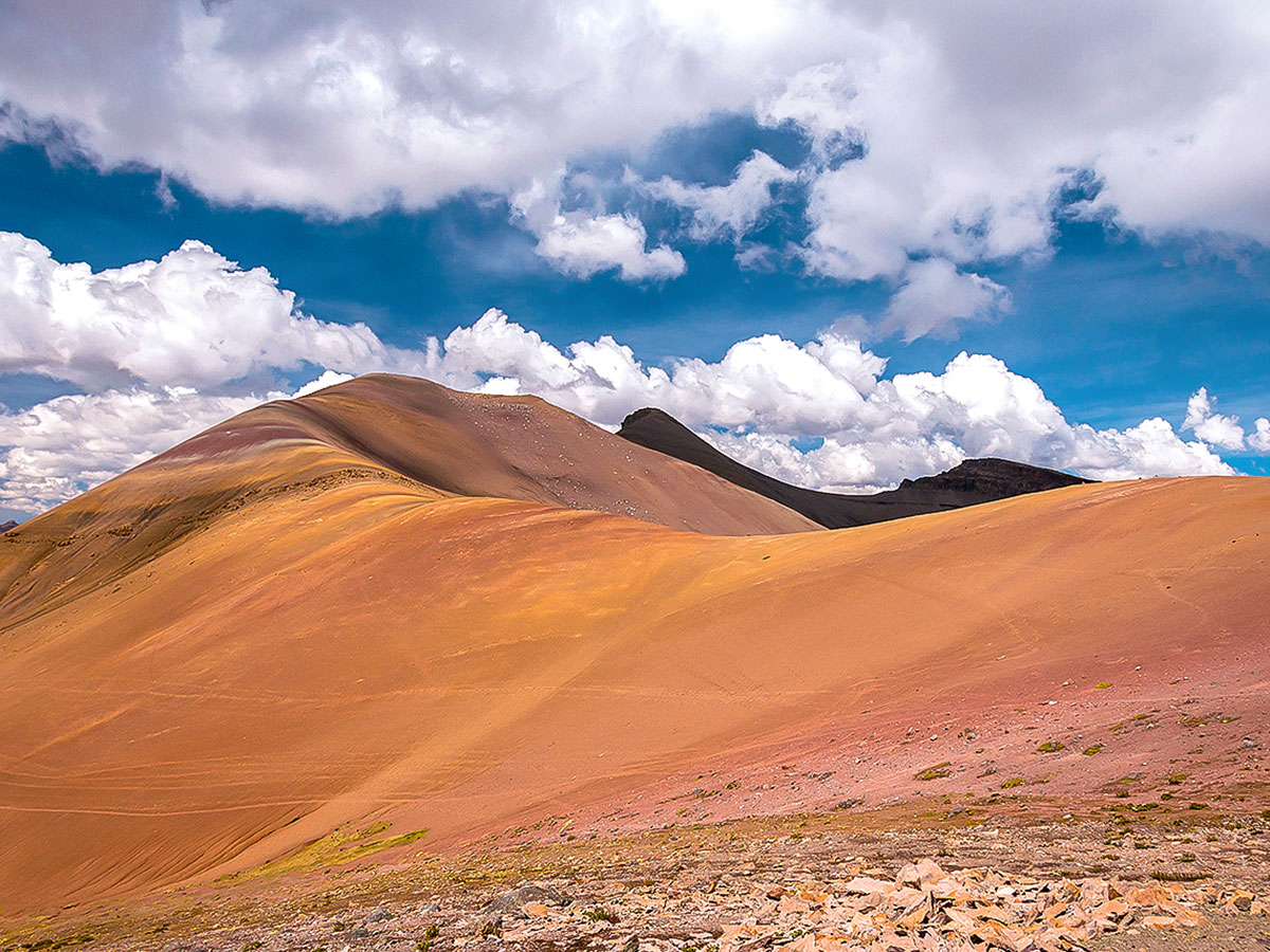 Long ridge under a blue, partly cloudy sky on the striped Rainbow Mountains of Peru