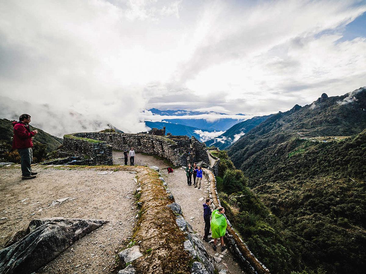 Hikers and Incan ruins on Inca Trail to Machu Picchu near Cusco Peru