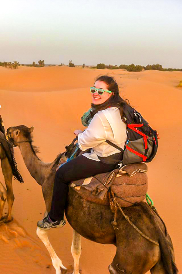 Happy trekker riding a camel on Erg Chigaga Tour in Morocco