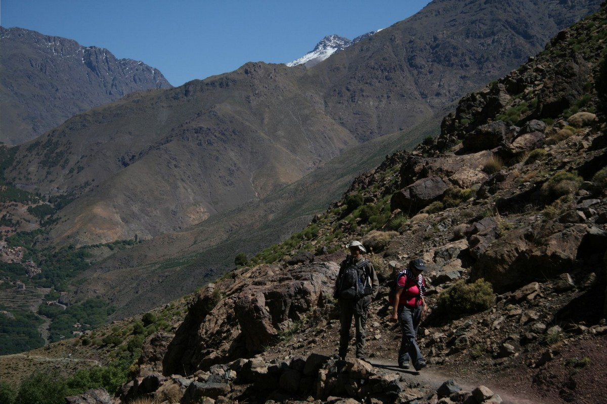Two hikers surrounded by beautiful views on guided trekking tour to Atlas Valley from Marrakech Morocco