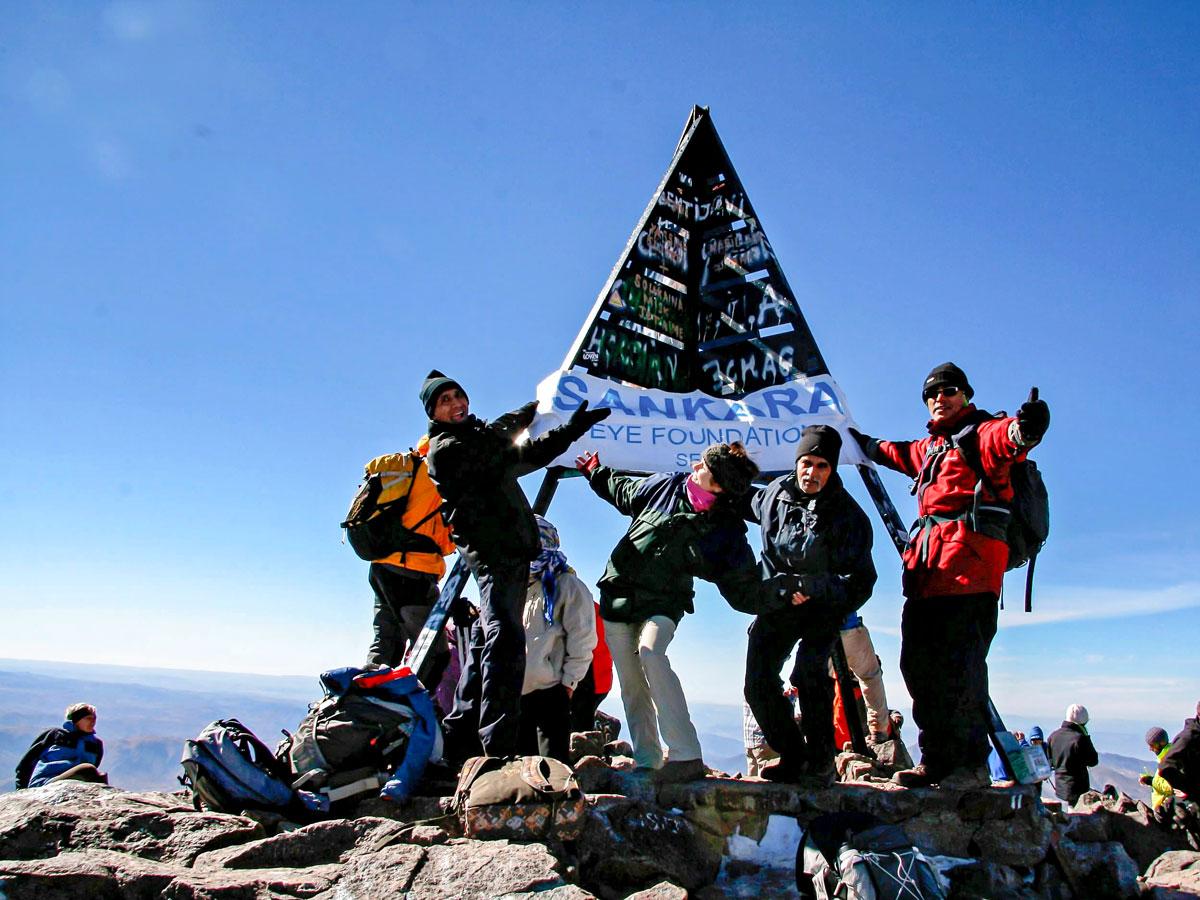 Posing on the peak of Mt Toubkal on Mt Toubkal Circuit Trek in Morocco
