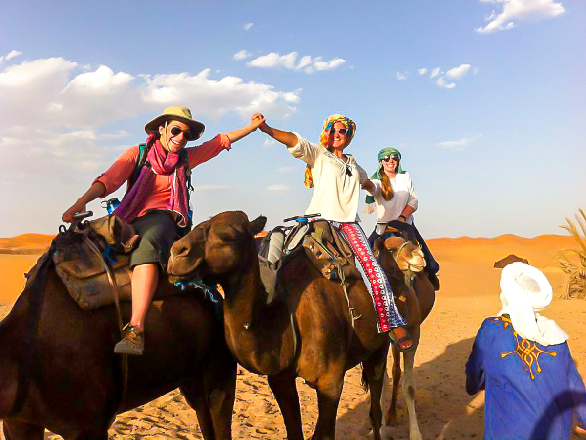 Group of happy trekkers riding camels on Merzouga Overland Tour in Morocco