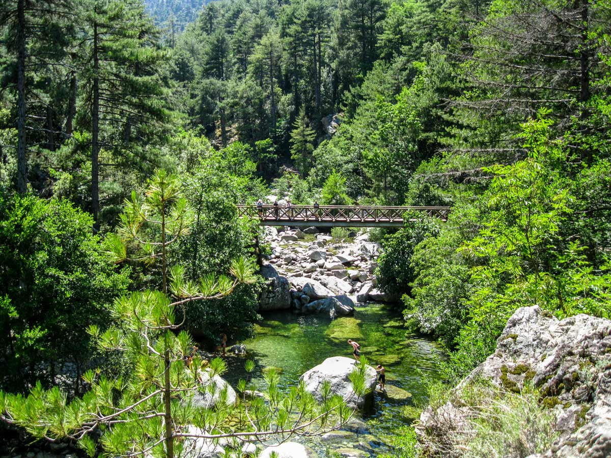 Hikers resting on a bridge near beautiful river on Mare a Mare North trek in Corsica
