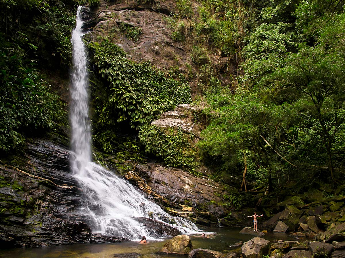 Swimming under the waterfall on Lost City Trek in Colombia