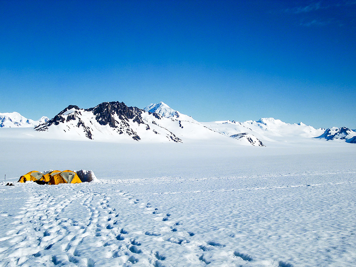 Expansive snow field and yellow tents seen on Patagonias Icefield Trek