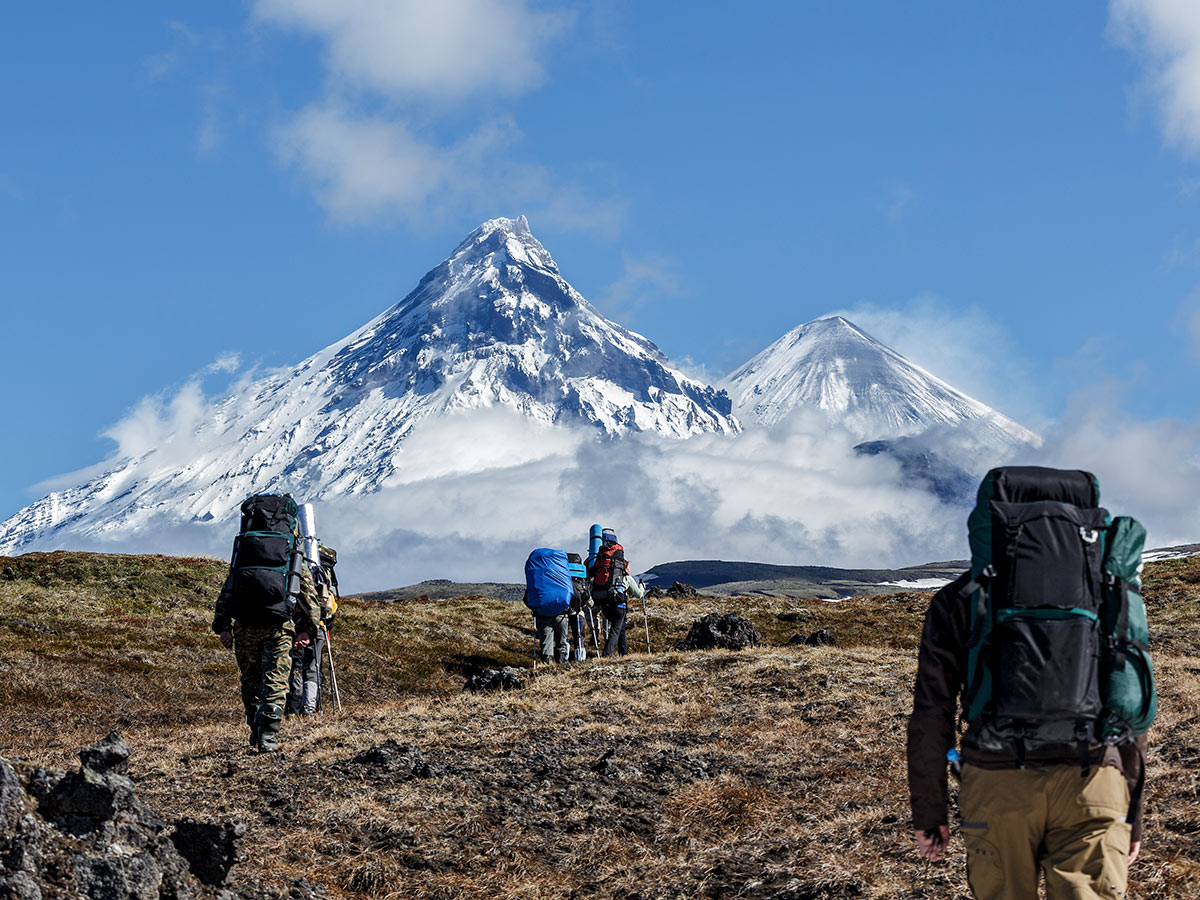 Trekkers near big mountains on a guided trek of Classic Kamchatka Trekking Tour
