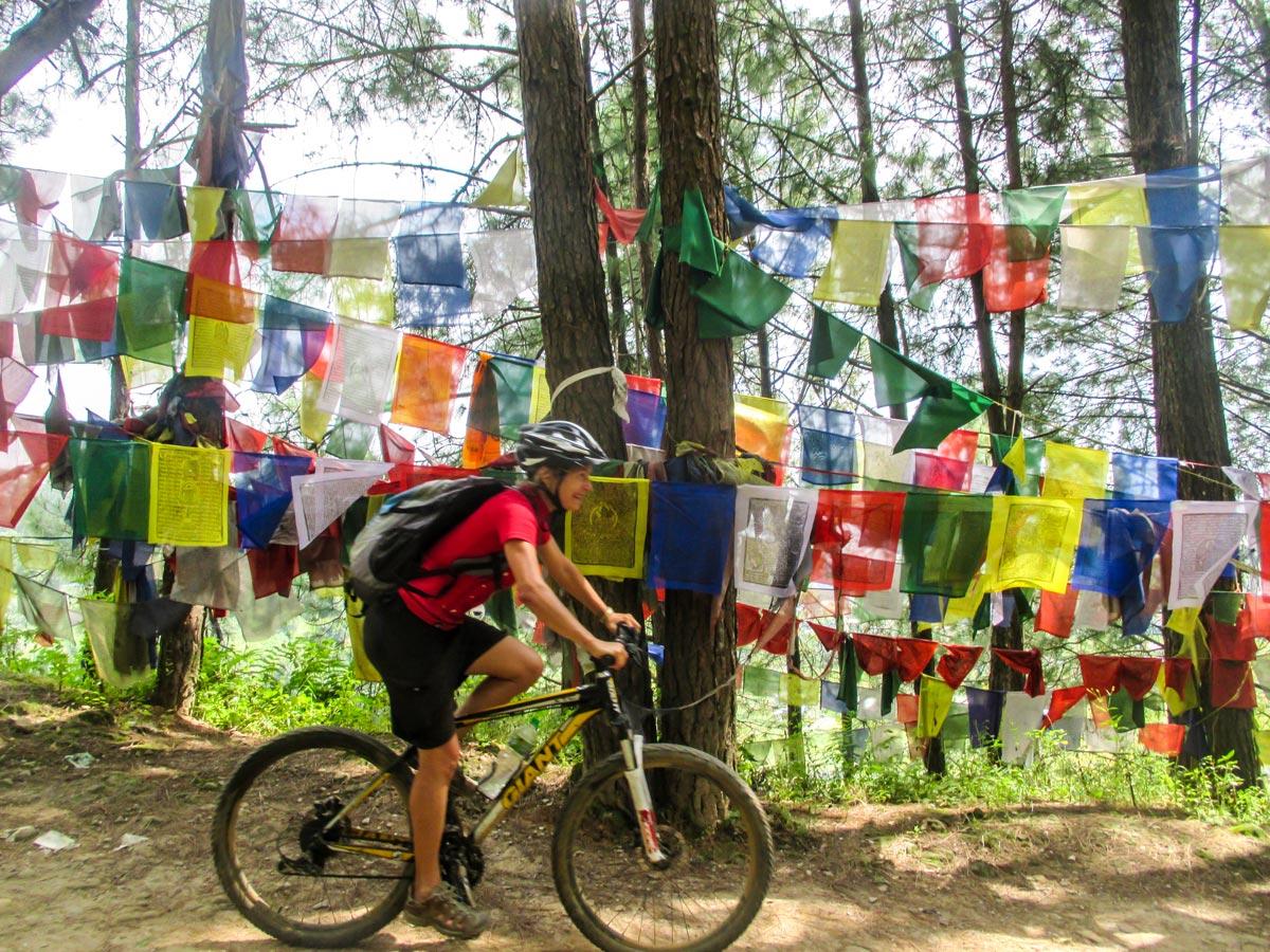 Biker and prayer flags on Cycling around Kathmandu Tour in Nepal
