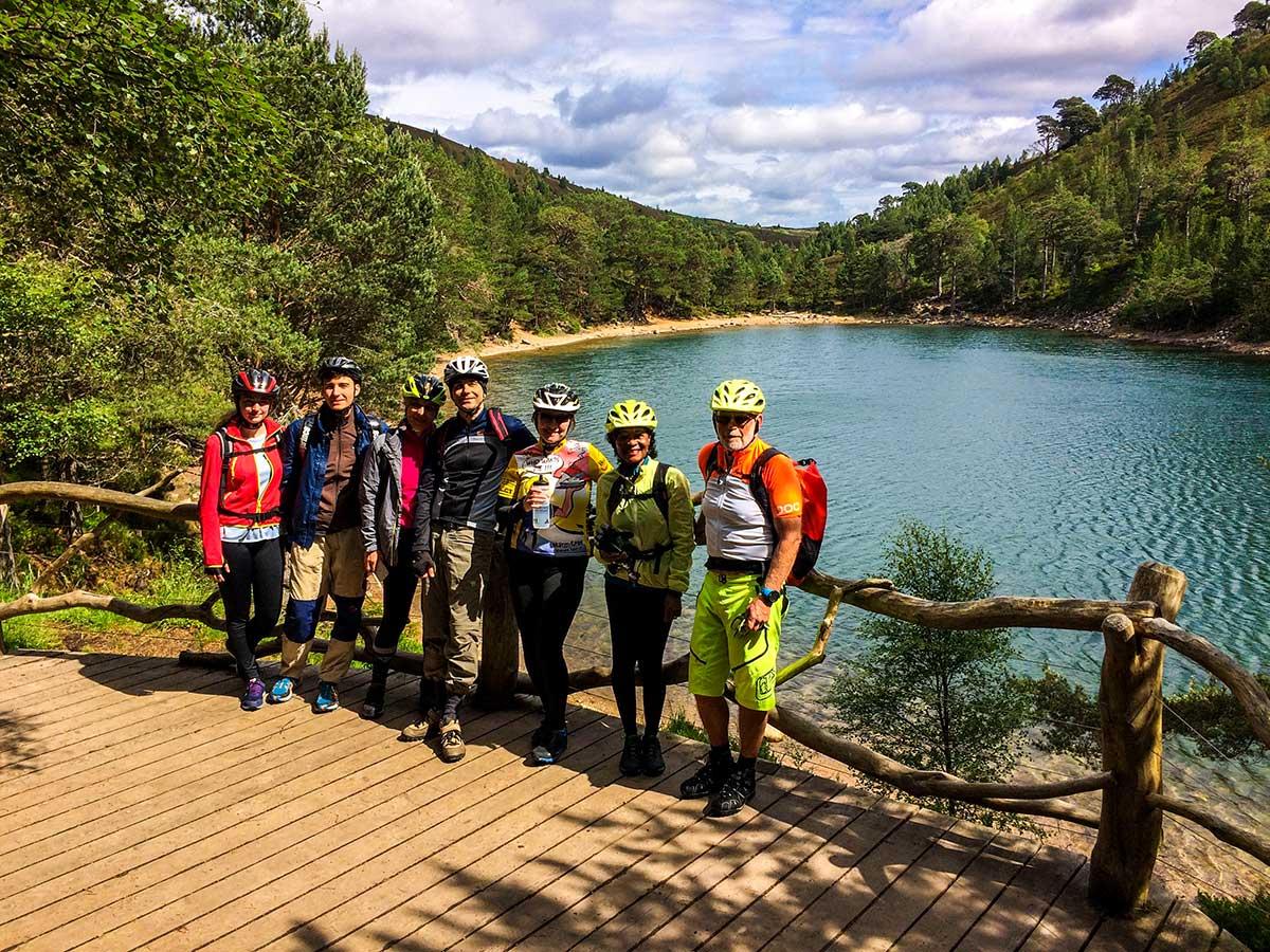 Group of bikers posing near beautiful lake on Mountain Biking across Scotland tour with guide