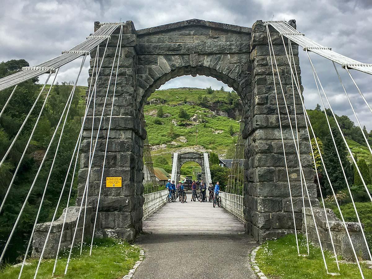 Mountain Bikers on a medieval stone bridge while on Mountain Biking across Scotland tour with guide