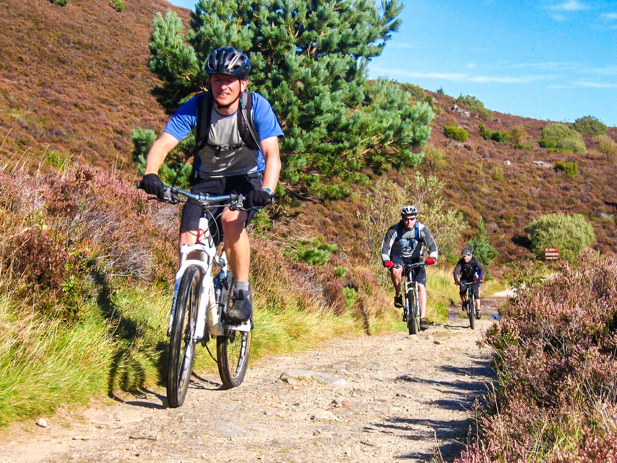 Three bikers riding on a rocky path of Mountain Biking across Scotland tour