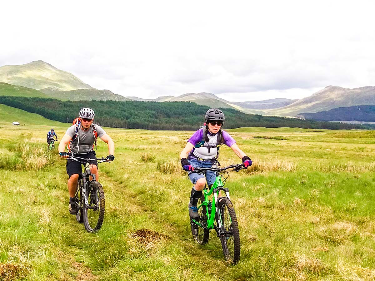 Two mountain bikers in the surroundings of Scottish Highlands on a guided biking tour