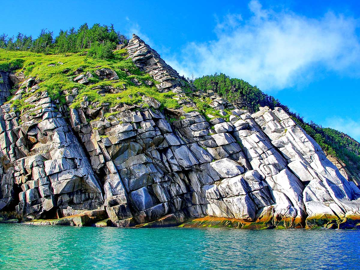 Colorful steep shores of Shantar Islands seen on Expedition to Shantar Islands Tour in Russia