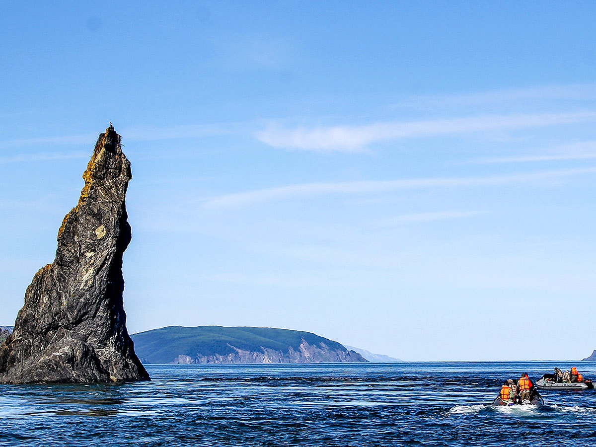 Group of people in motorboats swimming among the sharp rocks of Shantar Islands