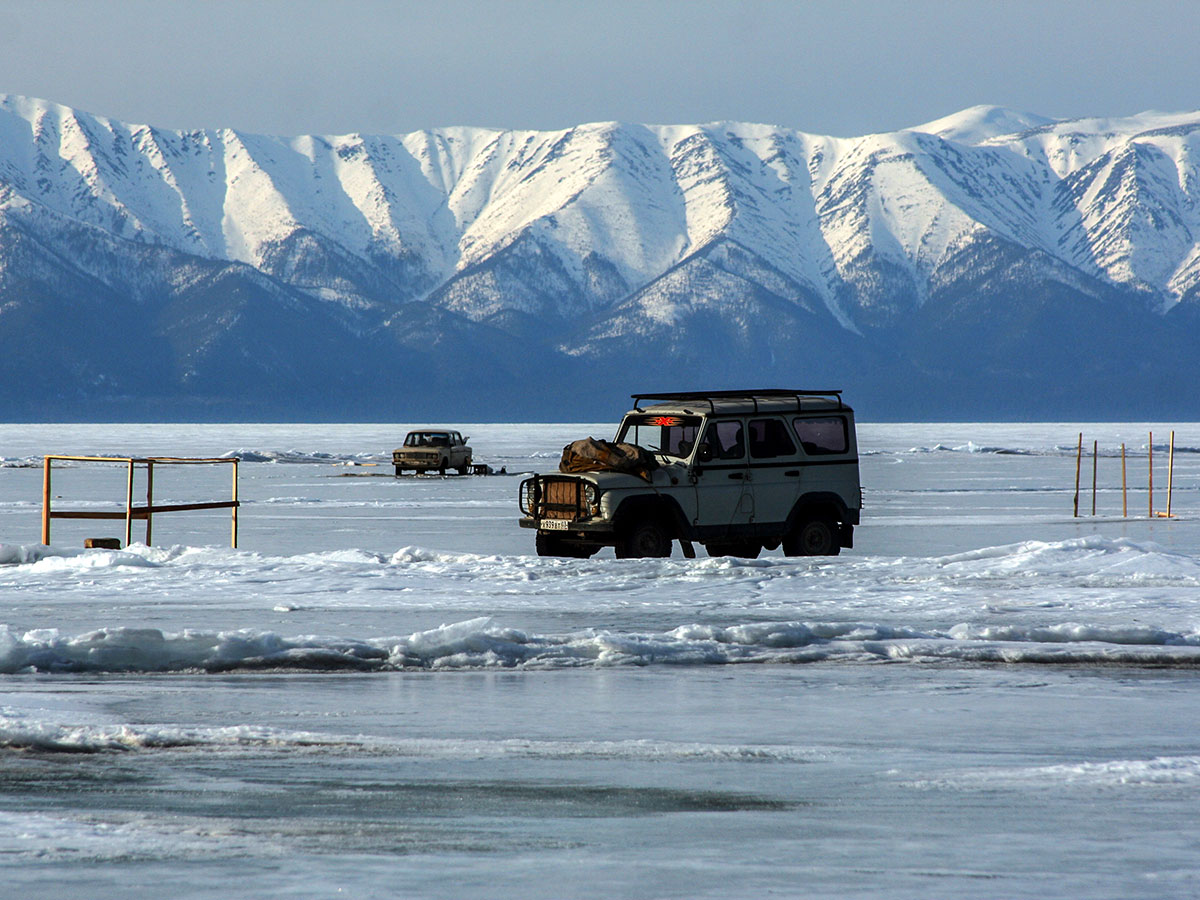 Two vehicles on frozen Lake Baikal on Grand Crossing of Lake Baikal Tour in Russia