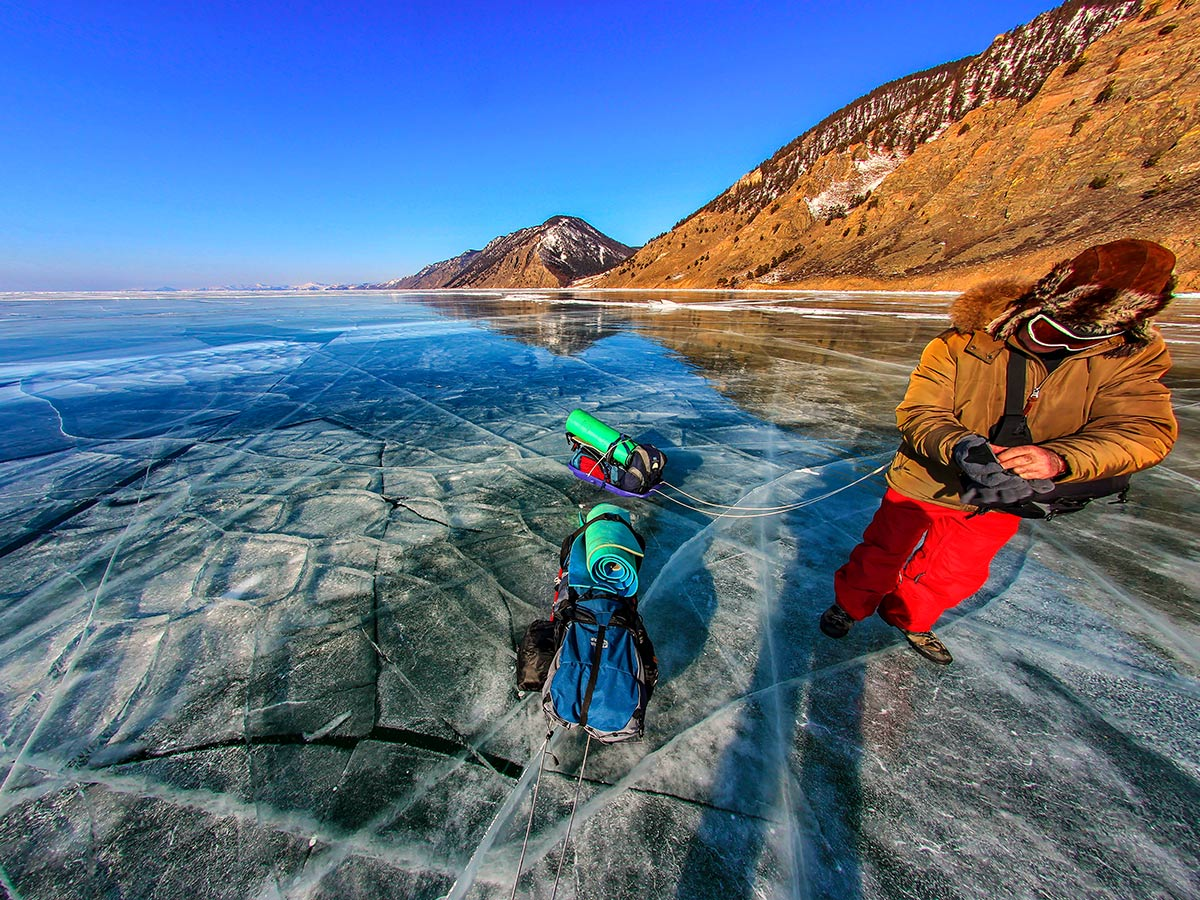 Hiker on a frozen Lake Baikal on Grand Crossing of Lake Baikal Tour with a guide