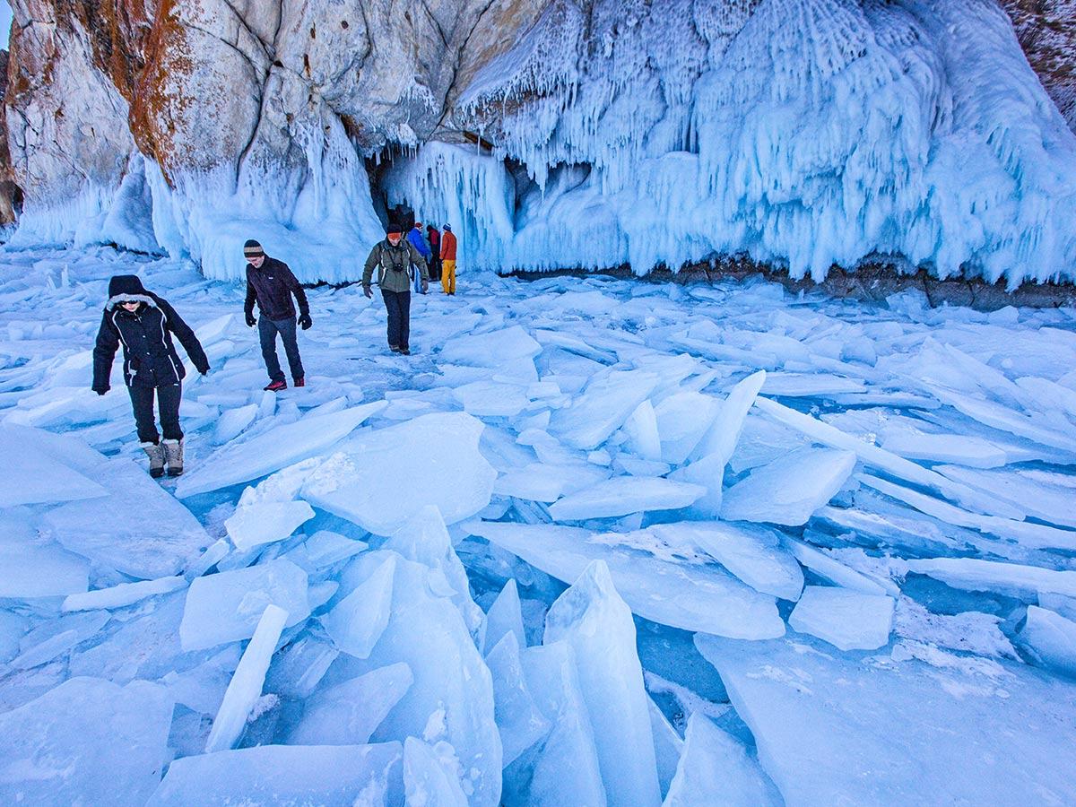 Group of trekkers walking near ice caves on Grand Crossing of Lake Baikal Tour