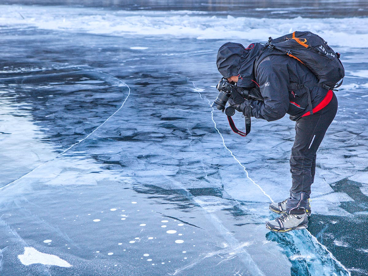 Curious hiker taking pictures of frozen Lake Baikal