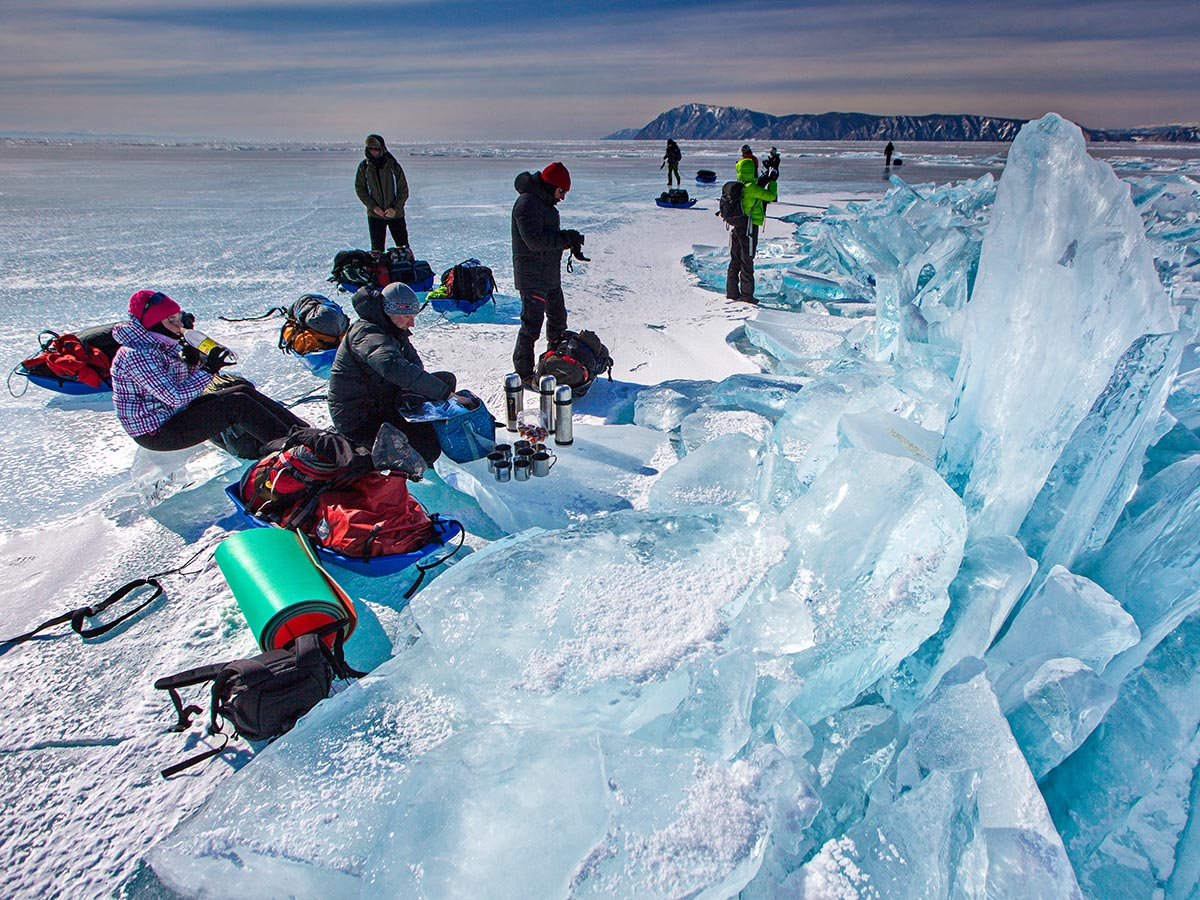 Group with a guide resting near beautiful ice formations on Baikal Lake