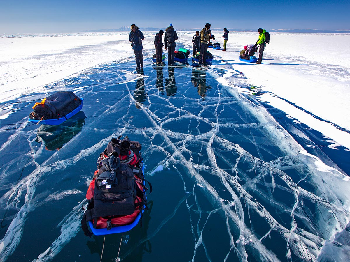 Guided group of hikers resting on frozen Lake Baikal on Grand Crossing of Lake Baikal Tour