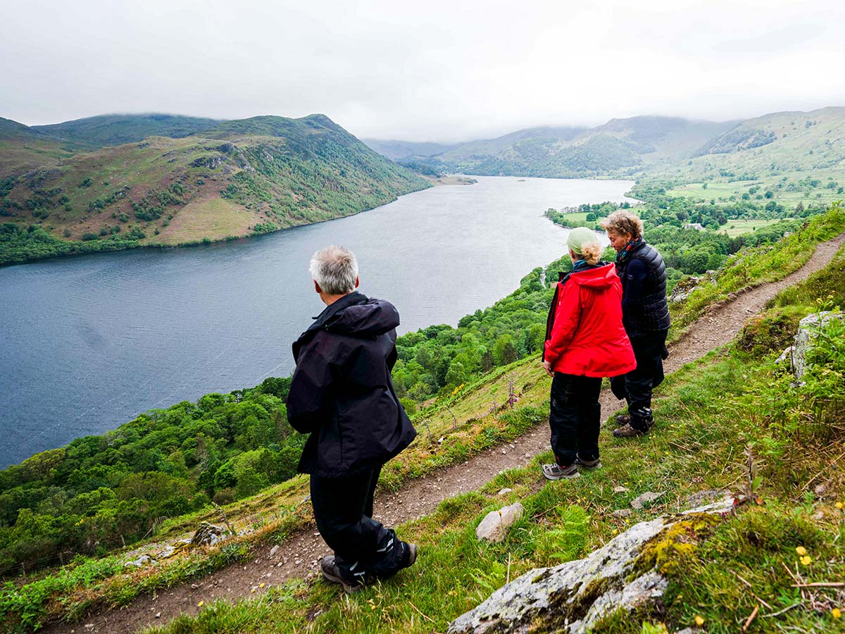 Three hikers looking at the lake on Northumberland and the Lake District walking tour in England UK