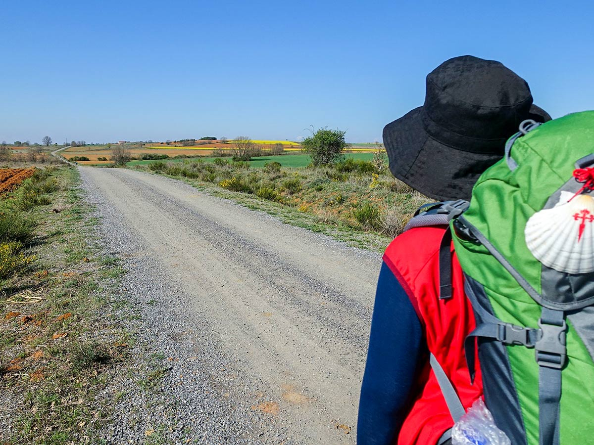Hiker with green backpack on Camino de Santiago Portuguese Way