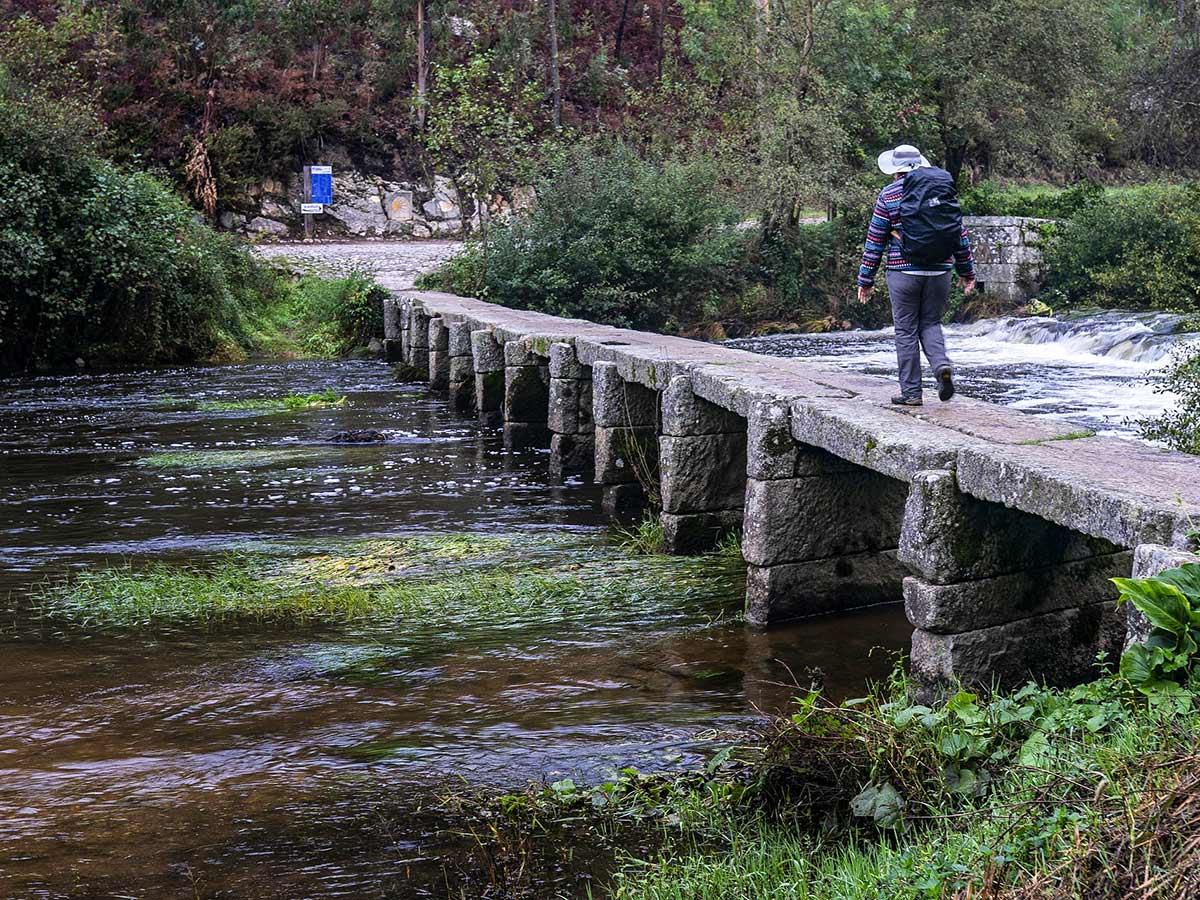 Lone hiker crossing the bridge on Camino de Santiago Portuguese Way in Spain