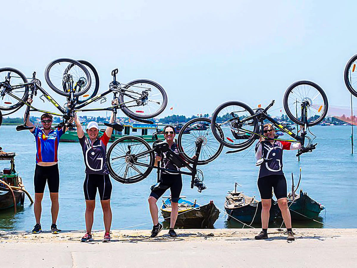 Group of bikers posing for picture on Coast of Vietnam Tour