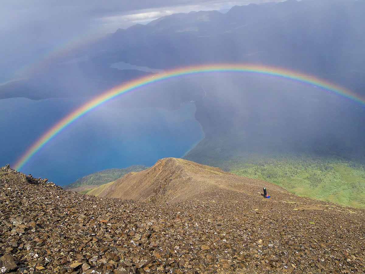 Raibow on a mountain over the valley in Canadian Rockies
