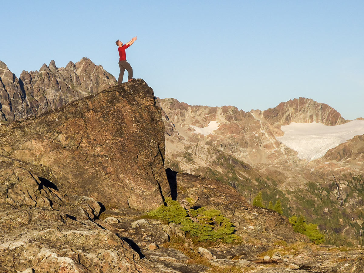 Hiker posing on a small peak in Vancouver Island on a guided camping tour