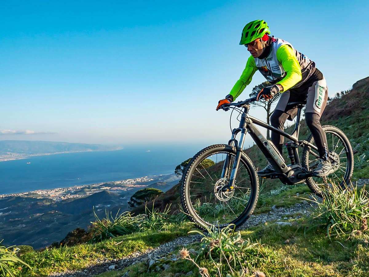 Biker admiring the beautiful views from the overlook in Sicily Island, Italy