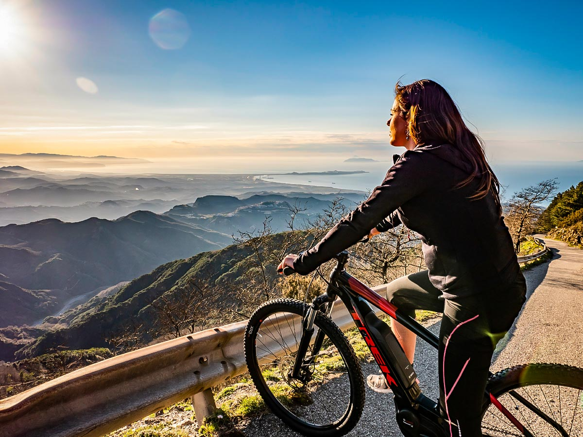 Biker looking down on the panoramic view of Sicily