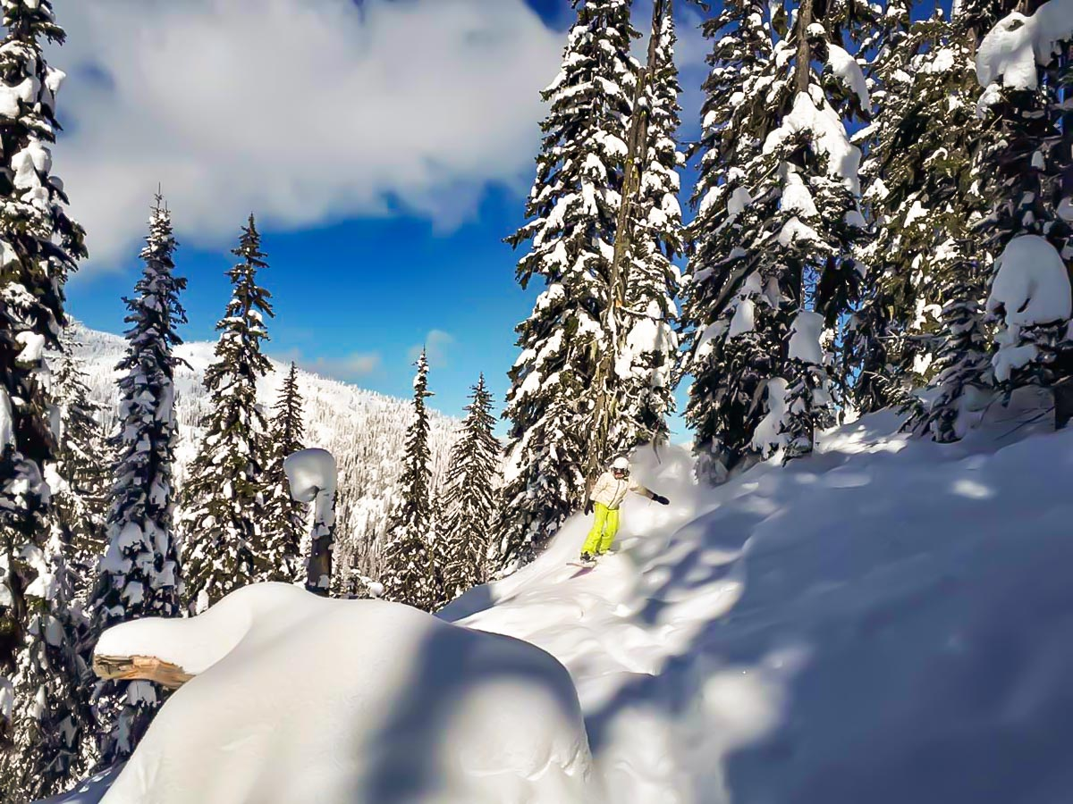 Snowboarder riding down on a snowed in mountain