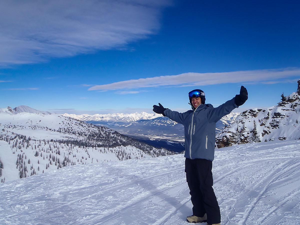 Skier posing on top of a snowy peak