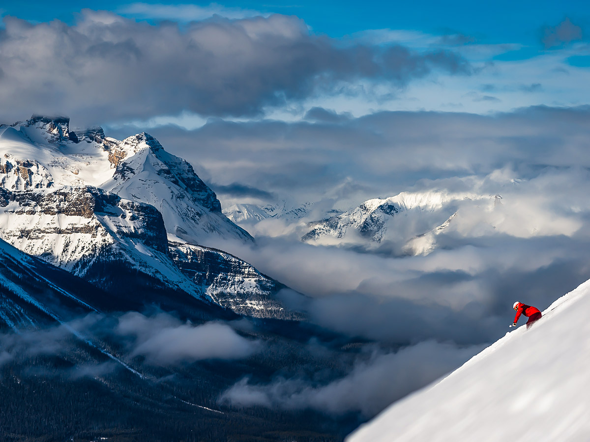 Skier riding down the powdery snow above the cloudy valley