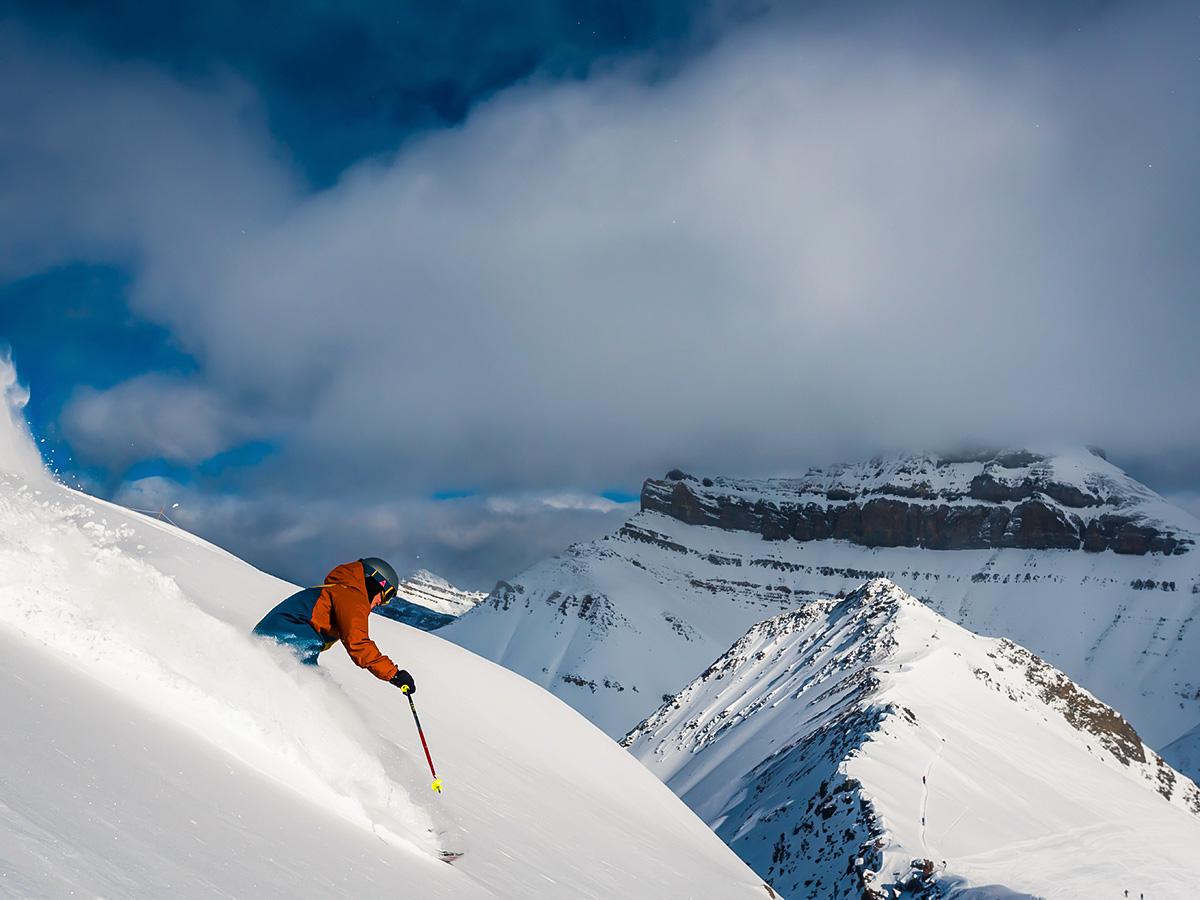 Riding down the steep mountain on a powdery snow