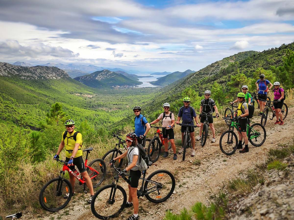 Group of bikers posing in front of the beautiful island on Mountain Biking in Croatian Islands Tour