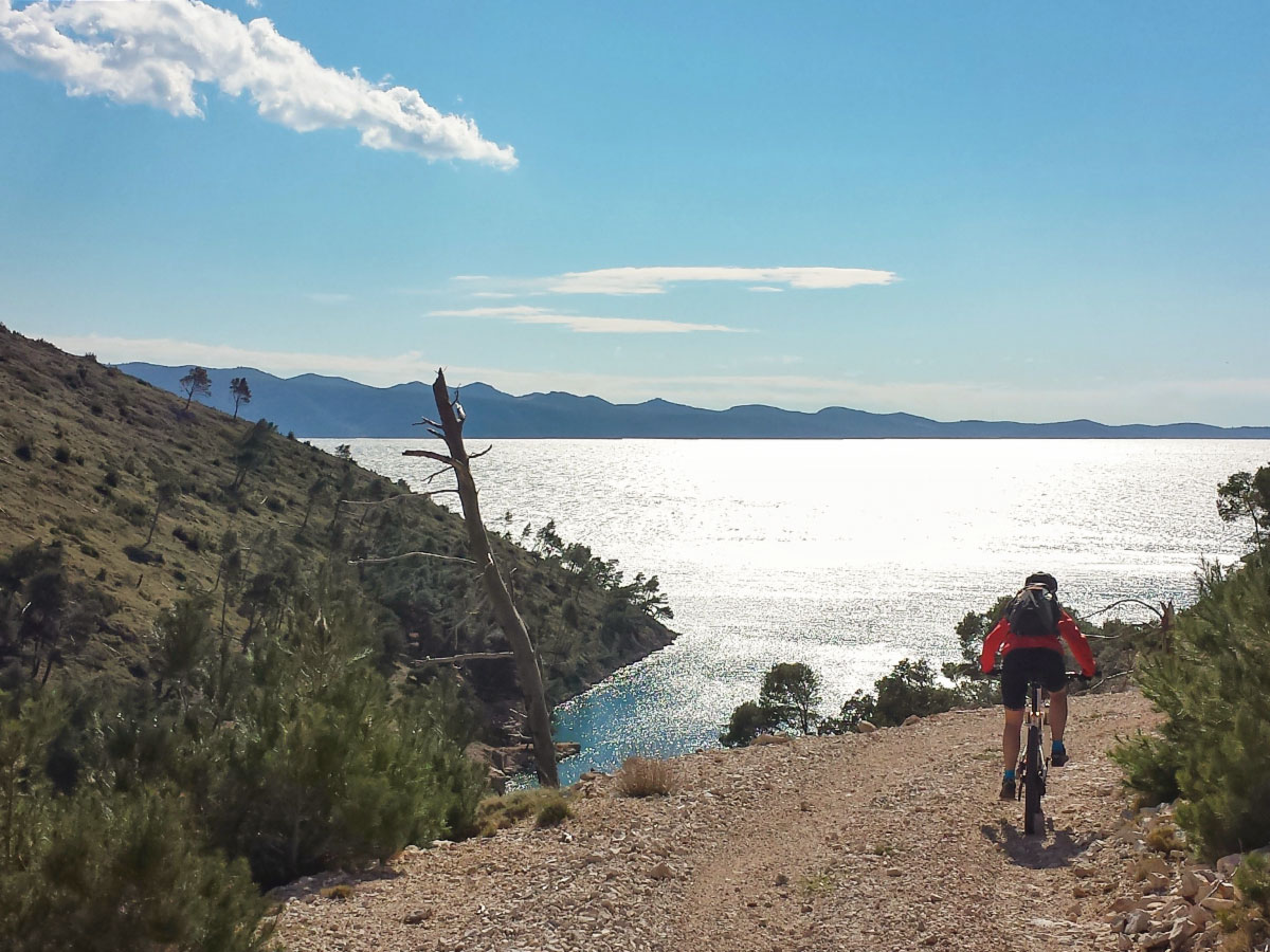 Biker approaching the Dalmatian Sea on a MTB tour in Croatian Islands