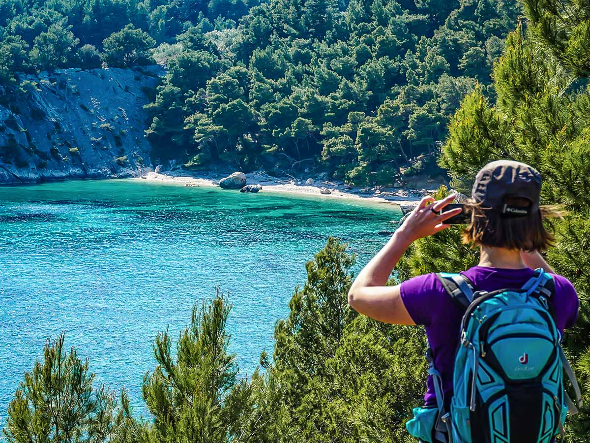 Hiker taking photos of the small secluded beach in Croatia on self guided hiking tour from Split to Dubrovnik