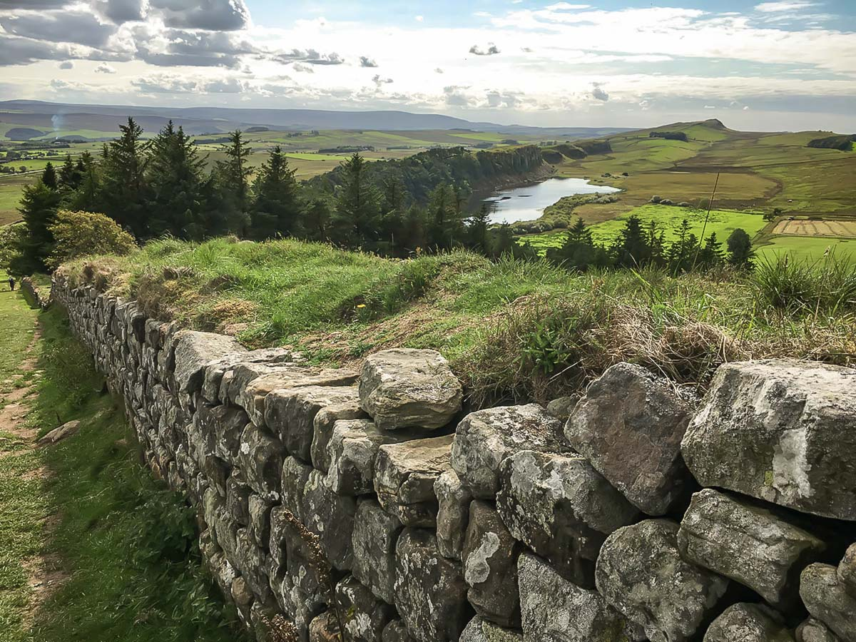 Approaching Broomlee Lough on a self-guided tour along the Hadrian s Wall Path to Lake District