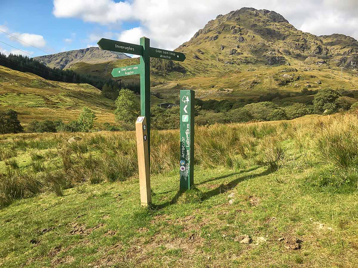 Signpost marking the Cowal Way surrounded by the beautiful mountains of Scotland