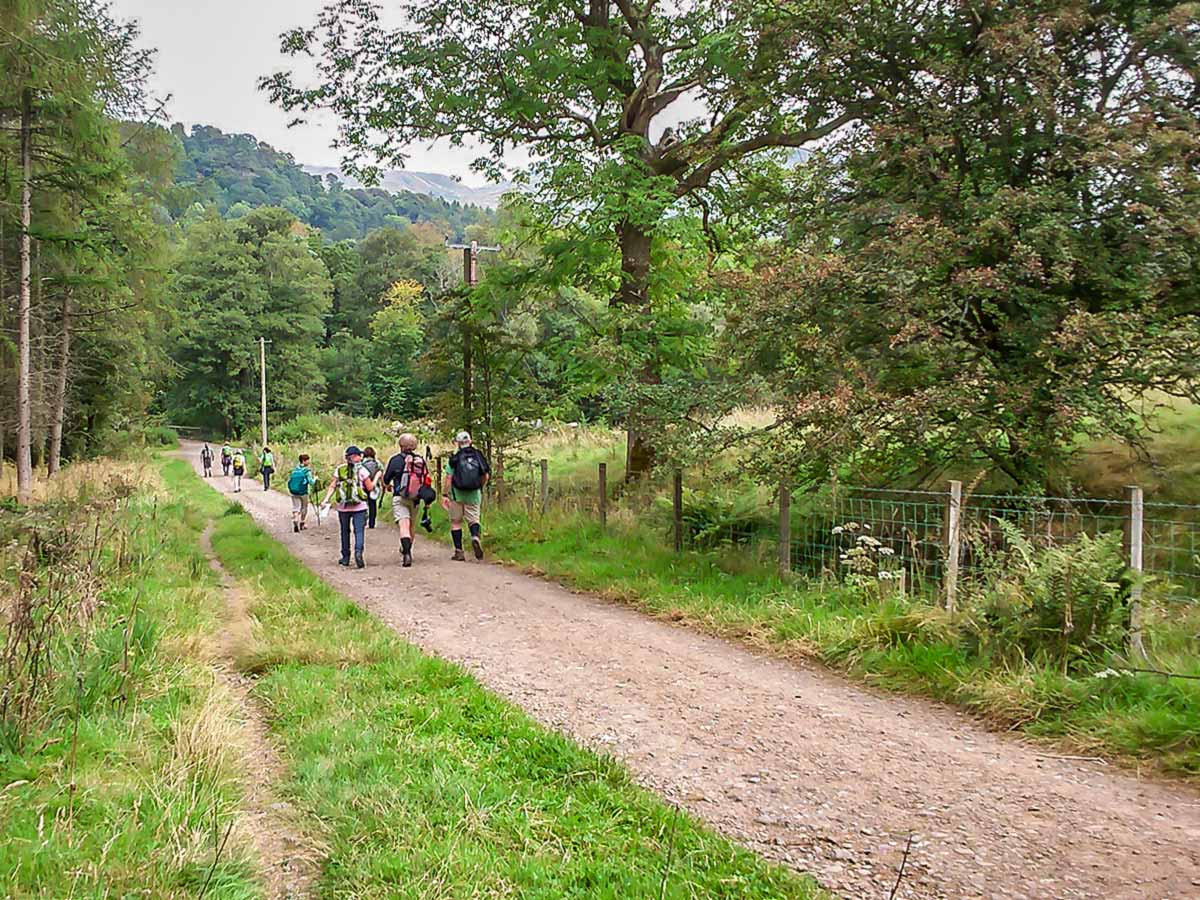 Group of hikers walking on a path of West Highland Way from Milngavie to Drymen