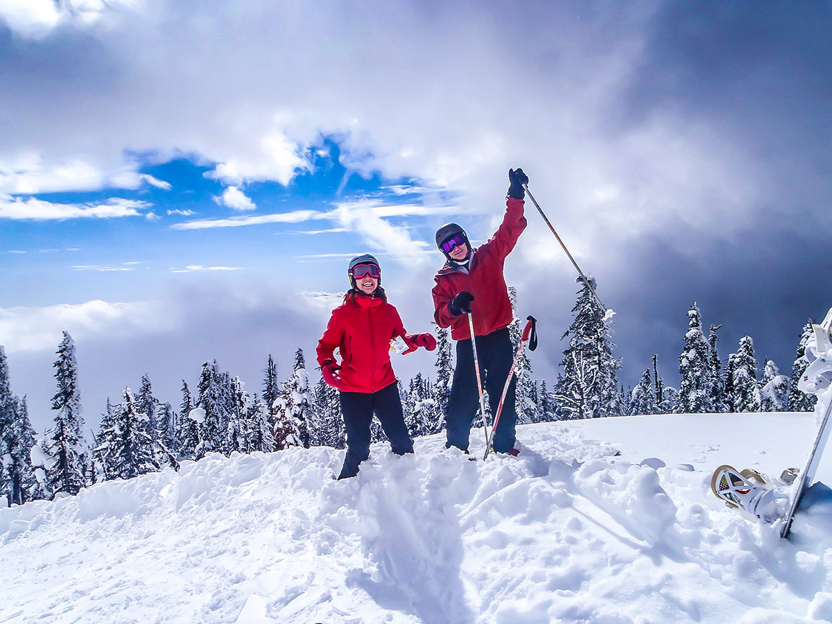 Two skiers posing on the mountain on a guided skiing trip in the Canadian Rocky Mountains