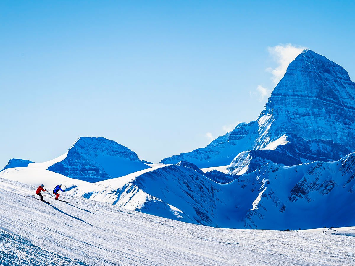 Mountain views and group of skiers in British Columbia, seen on a guided ski tour