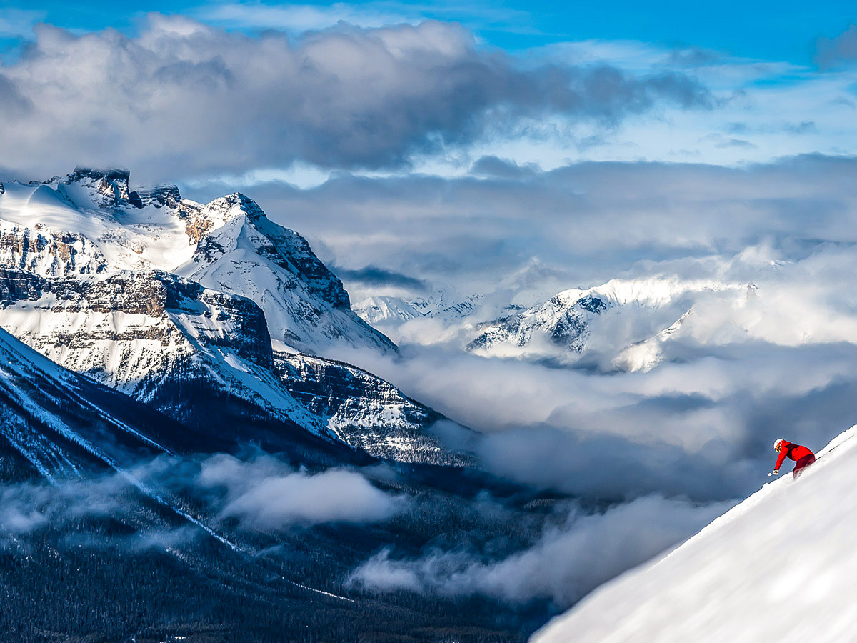 Skiing down the steep mountain in front of the stunning mountain views of the Canadian Rockies
