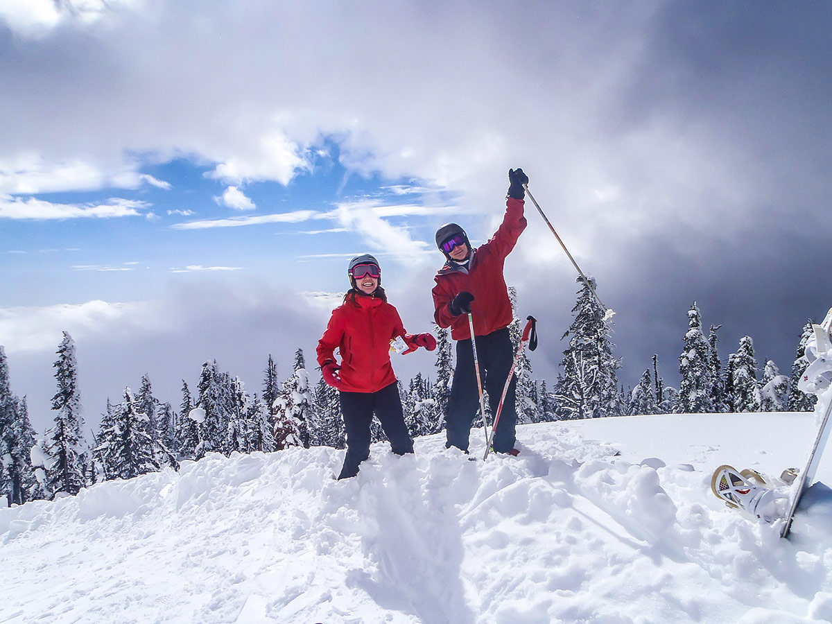 Two skiers posing in front of the beautiful mountain view in one of the British Columbias ski resorts