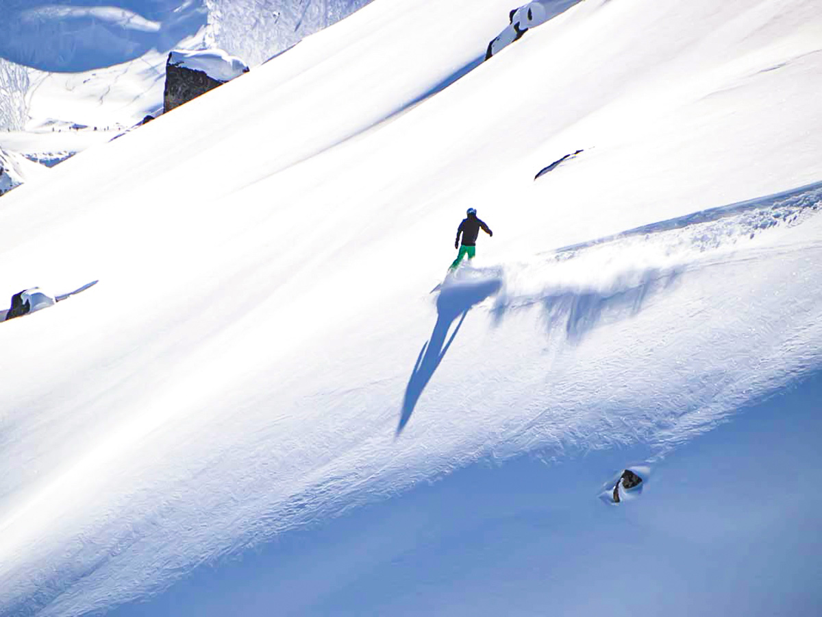 Skier going down the mountain on a guided 9 day ski trip in the Canadian Rockies