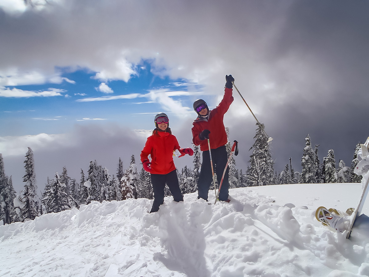 Two skiers posing in a snow on a guided skiing and snowboarding tour along the Powder Highway