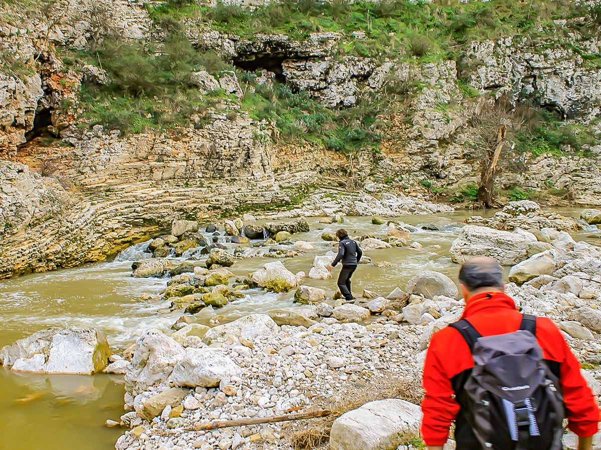 Two hikers crossing the creek on Puglia and Matera hiking tour