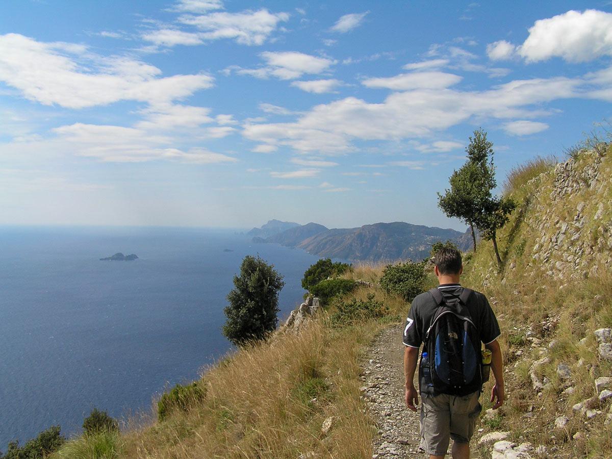 Hiker walking along the Mediterranean Sea coast on self guided Amalfi and Capri walking tour